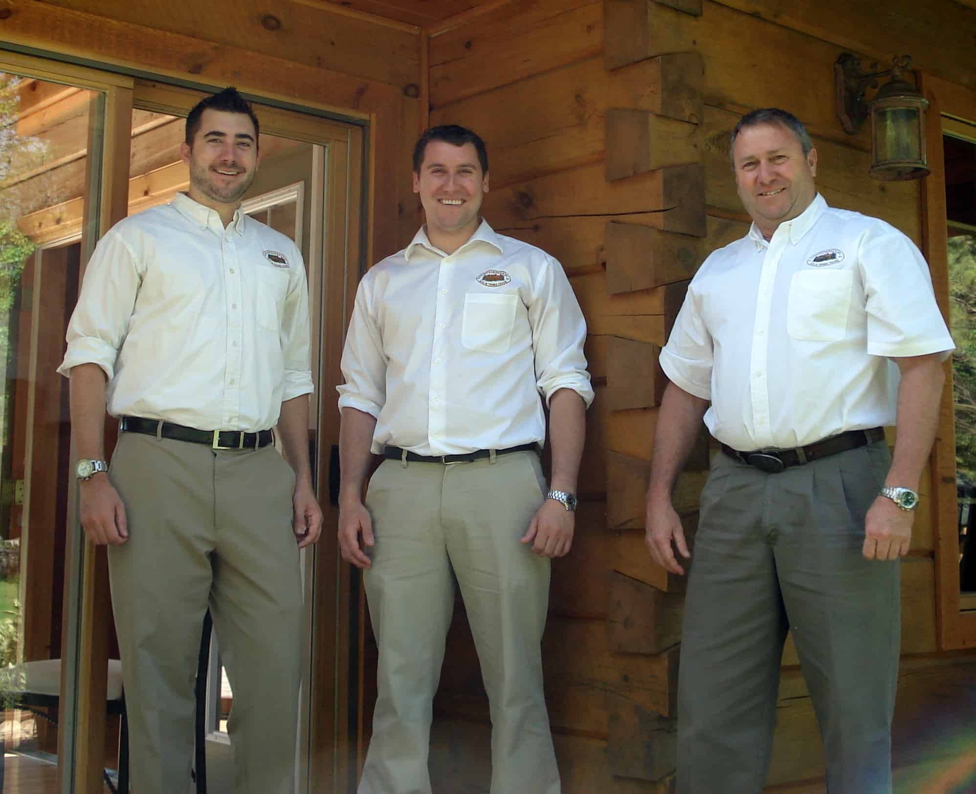 Photograph of Rich, Andy and Rick Kinsman standing in on the porch of an 1867 Confederation Log & TImber Frame home